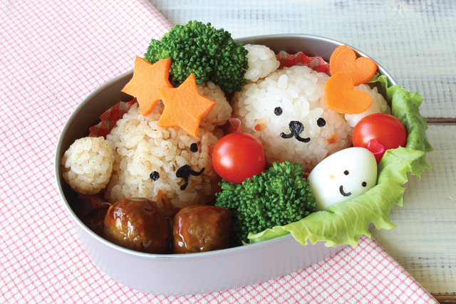 A bear-themed bento box lunch with little bears made out of rice, star and heart-shaped carrots, and a small egg with a smiley face.
