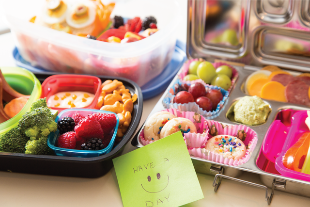 """A note that reads """"have a happy day"""" sits in front of several packed lunches."""