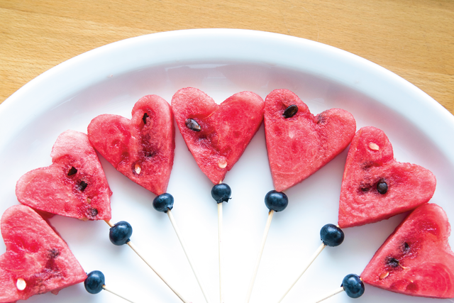 Pieces of heart-shaped watermelon on a spear with a blueberry accent underneath as part of a healthy school lunch.
